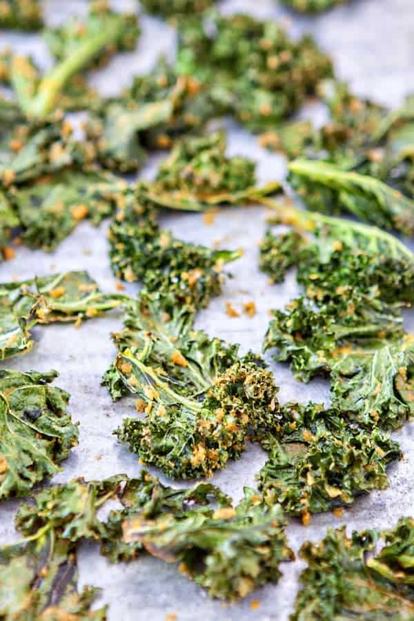 front view of baked kale chips coated with cheese on a baking tray