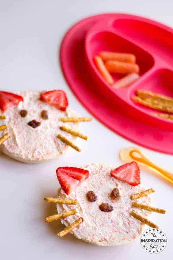 Angle view of a bagel with cream cheese with pretzel rods, strawberries and raisins shaped as a cat face