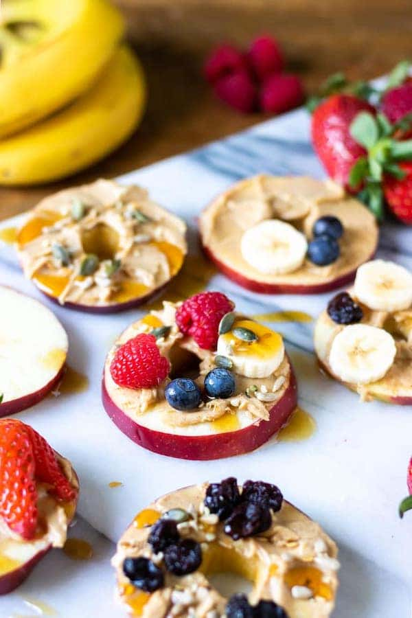 angle view of apple slices topped with fruits, peanut butter and nuts - after school snacks