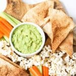 Top view of pita chips surrounded by veggies, popcorn and a green dip