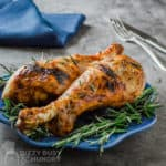 Side view of two turkey legs garnished with rosemary on a small blue plate with a blue napkin, fork and knife behind.