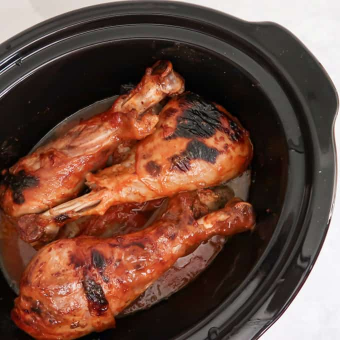 Overhead shot of three cooked turkey legs covered in homemade barbecue sauce in black crockpot.