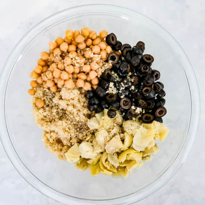 Close up shot of Chickpeas, black olives, cooked quinoa, artichoke hearts, and dressing in a clear bowl.