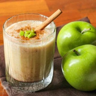 Smoothie with cinnamon, cut up apples, and a cinnamon stick on top, in a clear glass, beside two granny smith apples.
