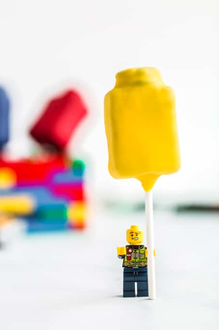 front view of a yellow lego man holding a yellow cake pop