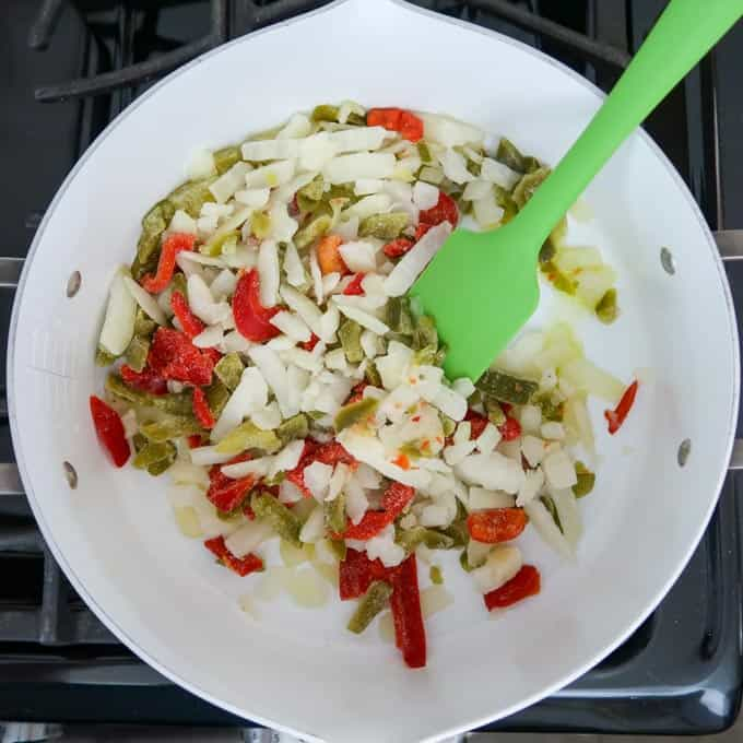 Overhead shot of olive oil, peppers, and onions in a white sauce pan on the stove.