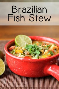 Side view of red pot with fish stew and a garnish of cilantro and lime.