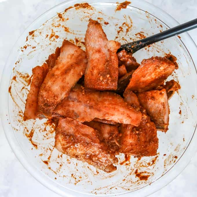 Close up view of tilapia coated with orange-red marinade in a clear bowl.