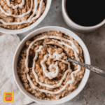 top view of steel cut oats in a white bowl with a simple cream cheese frosting swirl