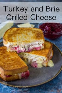 Side view of three stacked halves of brie grilled cheese with cranberry sauce and sliced cheese on a blue background.