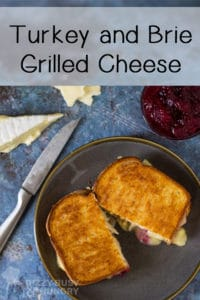 Overhead view of sliced halves of brie grilled cheese with a knife, sliced cheese, and cranberry sauce on a blue background and plate.