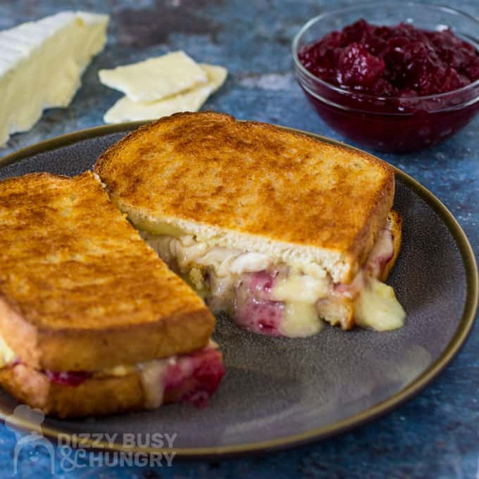 Side view of brie grilled cheese in halves with a small bowl of cranberry sauce and sliced cheese with a blue background.