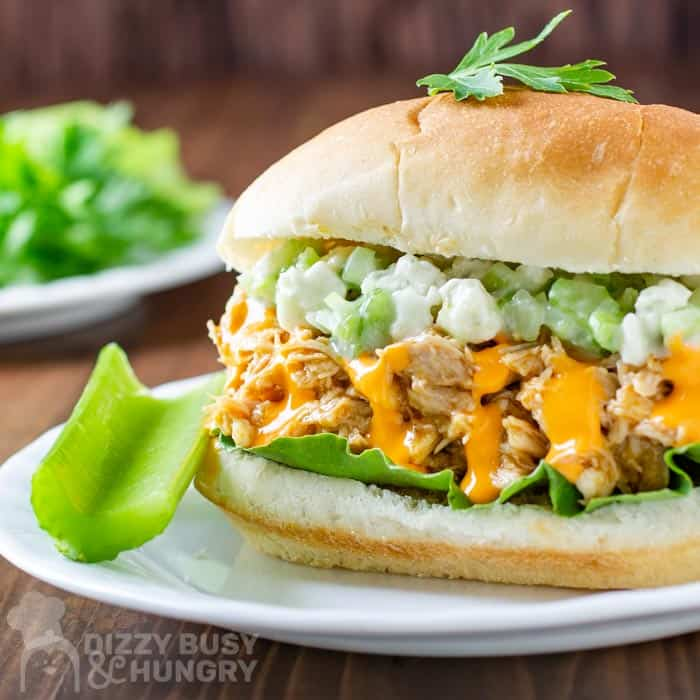 Side view of buffalo chicken sandwich with a side of celery on a white plate and wooden background.