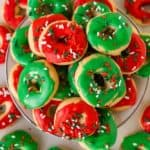 Top view of several mini donut-shaped cookies with red and green frosting on top and sprinkles - Easy Christmas Cookies