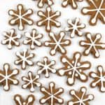 Top view of gingerbread cookies shaped like snowflakes and topped with white icing.