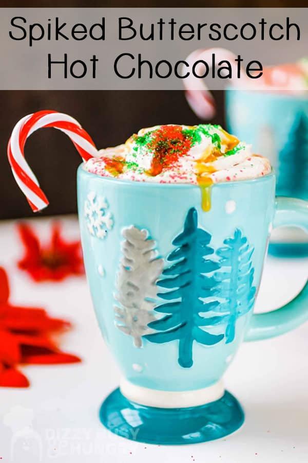 Side view of hot chocolate with whipped cream and a candy cane in a blue mug with a white background.