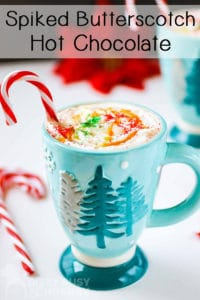 Close up shot of hot chocolate with whipped cream and a candy cane in a blue mug with a white background.