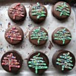 Top view of Oreos covered in chocolate and topped with Christmas tree shaped frosting