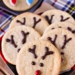Top view of 6 sugar cookies decorated with Reindeer face and antlers. In the back a cookie with christmas lights decoration is visible - Easy Christmas Cookies