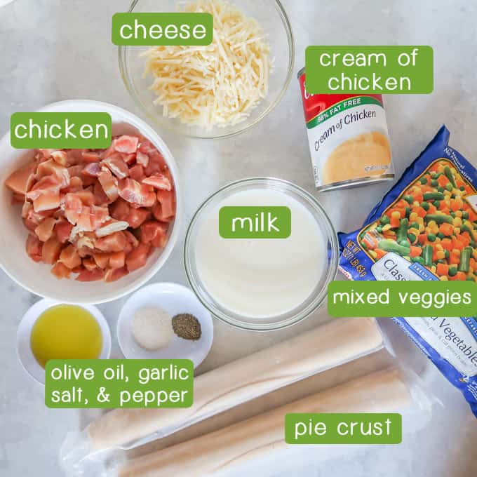 Overhead shot of ingredients- chicken, cheese, milk, cream of chicken, mixed veggies, pie crust, olive oil, garlic salt, and pepper.