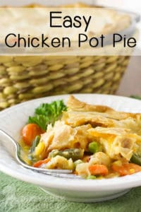 Side view of chicken pot pie in a white bowl with a fork and a wicker basket in the background.