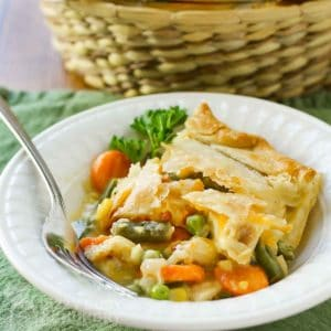 Side view of chicken pot pie in a white bowl with a fork and a green background.