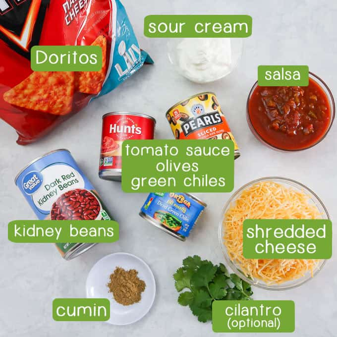 Overhead shot of ingredients- Doritos, sour cream, salsa, tomato sauce, olives, chives, kidney beans, shredded cheese, cumin, and cilantro.