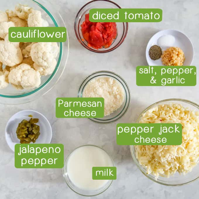 Overhead shot of ingredients- cauliflower, diced tomato, salt, pepper, garlic, Parmesan cheese, pepper jack cheese, jalapeño pepper, and milk.