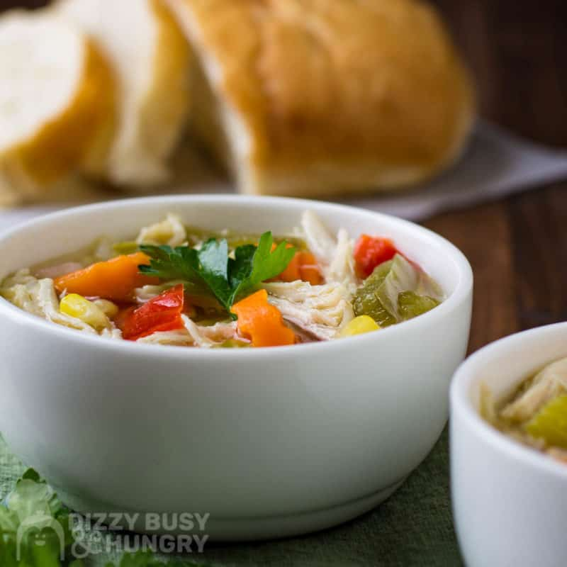 Side shot of chicken soup in a white bowl with sliced bread in the background.