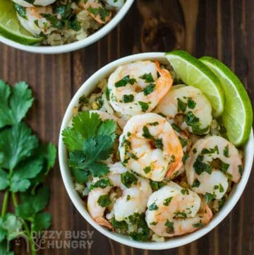 Overhead shot of shrimp in a white bowl with cilantro and lime garnish.