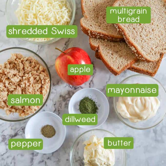Overhead shot of ingredients- Shredded Swiss cheese, multigrain bread, an apple, salmon, mayonnaise, dill weed, pepper, and butter.