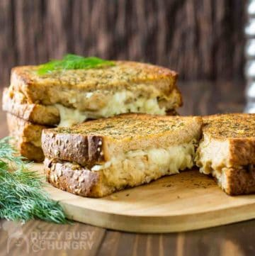 Side view of grilled cheese cut in half with dill on the side.