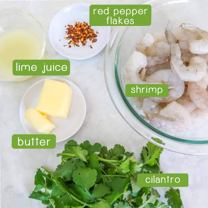 Close up shot of ingredients- shrimp, red pepper flakes, lime juice, butter, and cilantro.