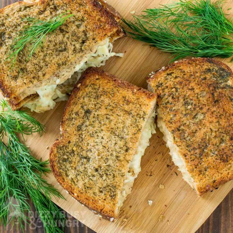 Overhead view of grilled cheese sandwich cut in half on a wooden cutting board garnished with dill weed.