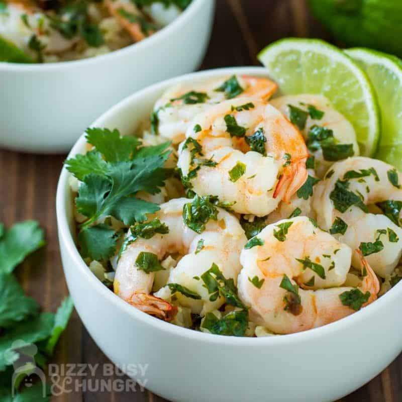 Side view of shrimp in a white bowl garnished with cilantro and lime.