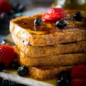 Close up shot of four stacked french toast covered in syrup, and garnished with strawberries and blueberries.