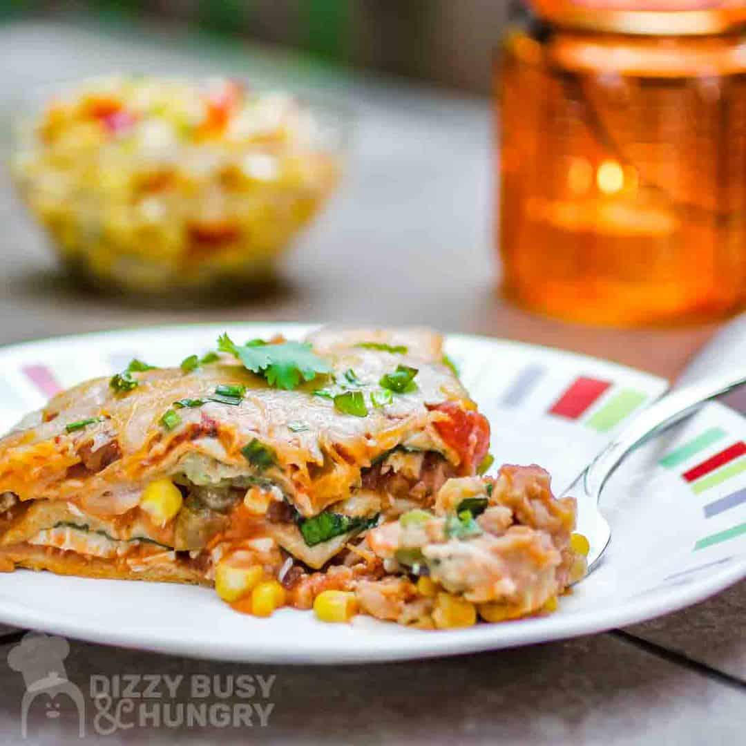 Side view of vegetarian Mexican lasagna garnished with green onions, on a colored plate.