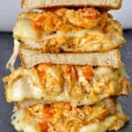 Extreme closeup of a buffalo and cheese sandwich stacked on top of each other