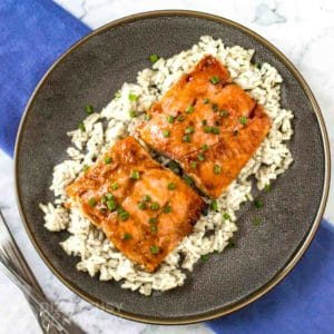 Close up shot of teriyaki glazed salmon on rice, garnished with chives on a brown plate with a blue background