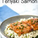 Side view of glazed teriyaki salmon on rice topped with chives on a brown plate with a blue background.