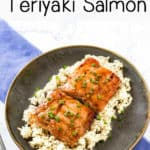 Side view of teriyaki glazed salmon on rice garnished with chives, on top of a brown plate with a blue background.