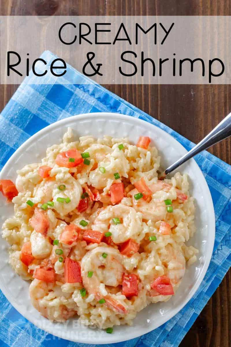 Overhead shot of creamy rice and shrimp on a white bowl with a fork on the side on a blue plaid cloth.