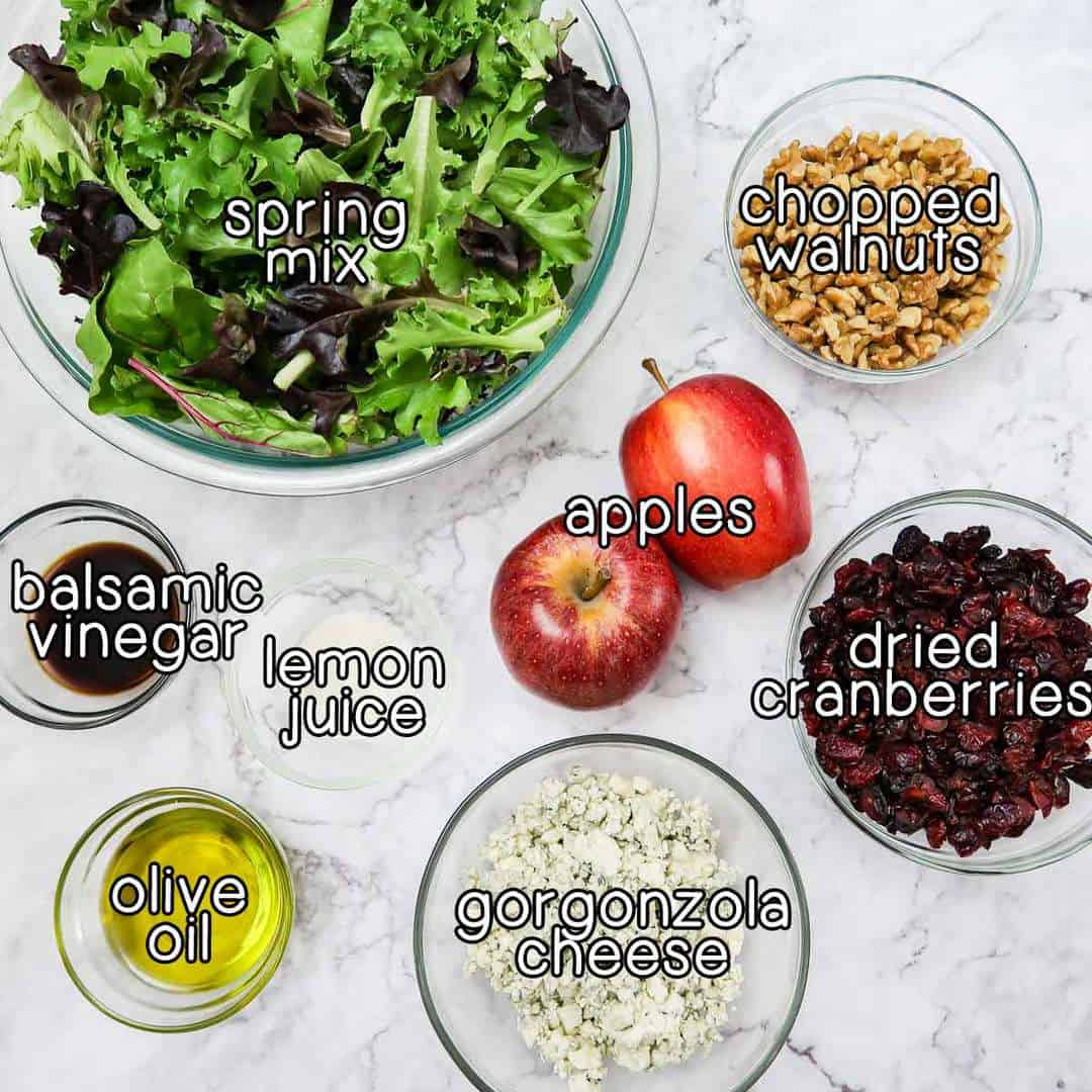 Overhead view of ingredients- spring mix, chopped walnuts, apples, dried cranberries, gorgonzola cheese, lemon juice, olive oil, and balsamic vinegar.