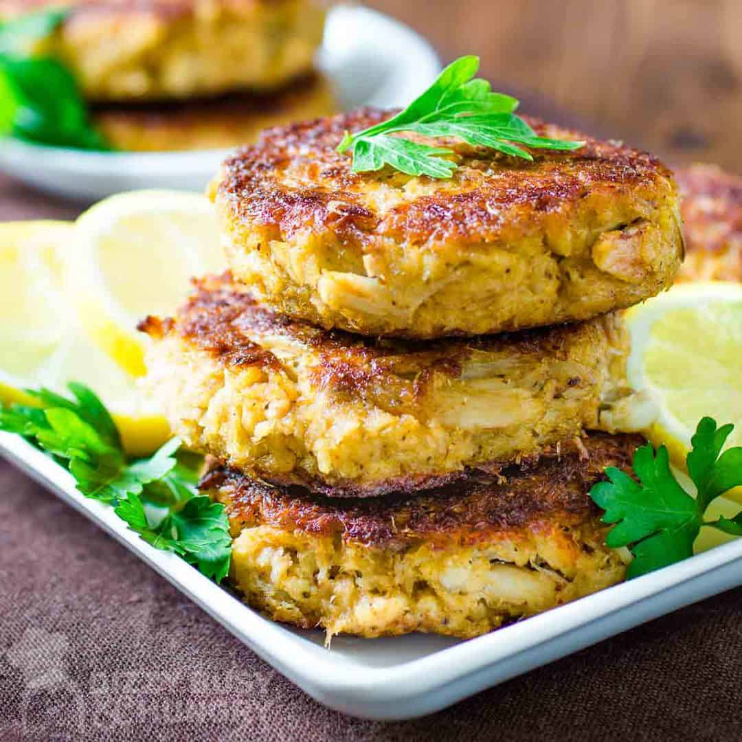 Side view of three crab cakes stacked on a white plate garnished with herbs and sliced lemons.