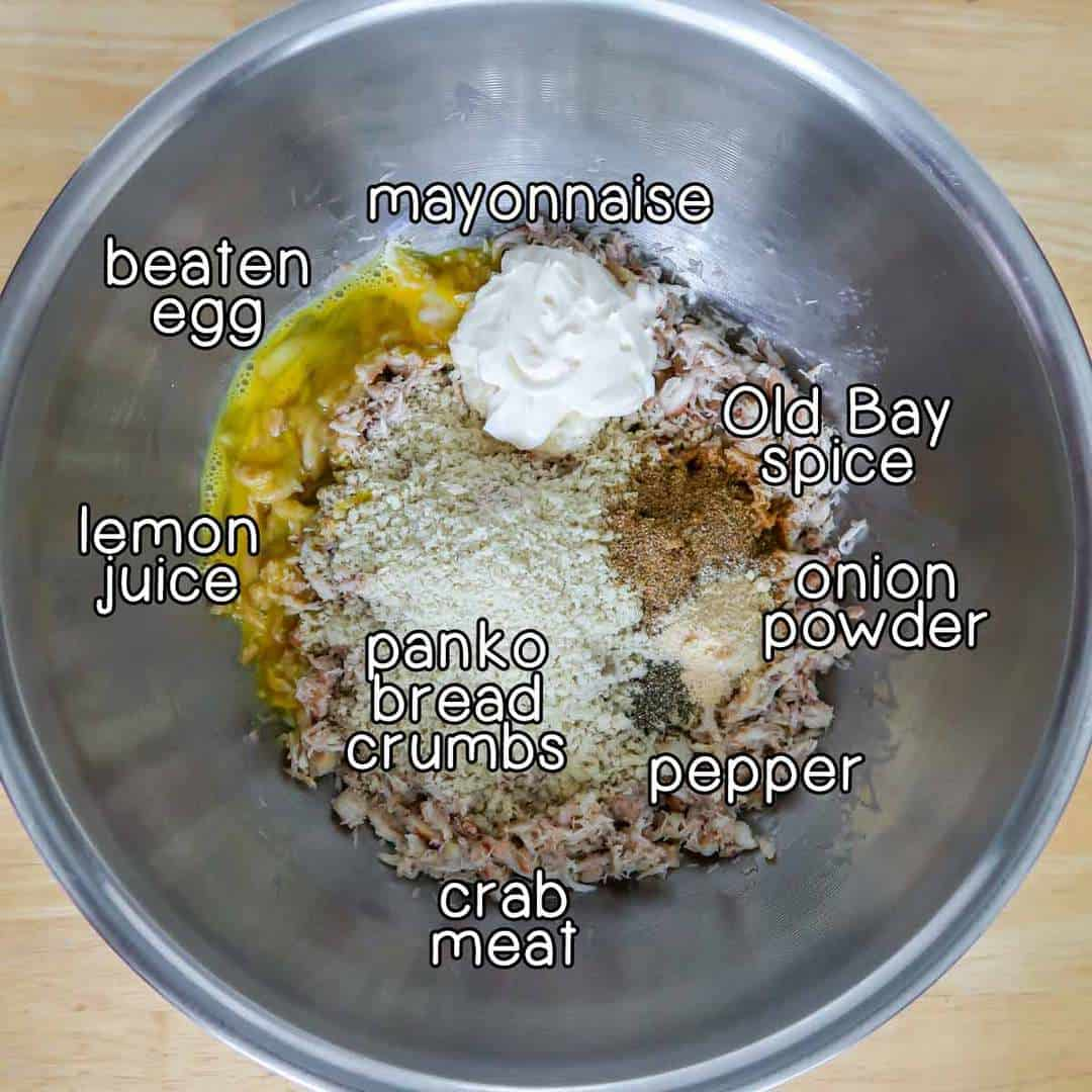 Close up shot of ingredients layered in a metal bowl- beaten egg, mayonnaise, old bay spice, onion powder, panko bread crumbs, lemon juice, pepper, and crab meat.