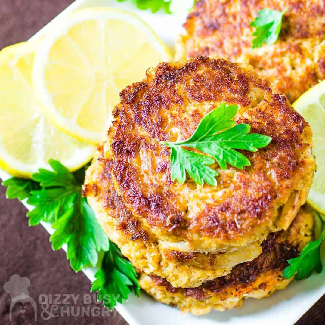 Overhead shot of three crab cakes stacked on a white plate garnished with herbs and sliced lemons.