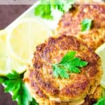 Overhead shot of three crab cakes stacked on a white plate on a bed of sliced lemons and herbs.