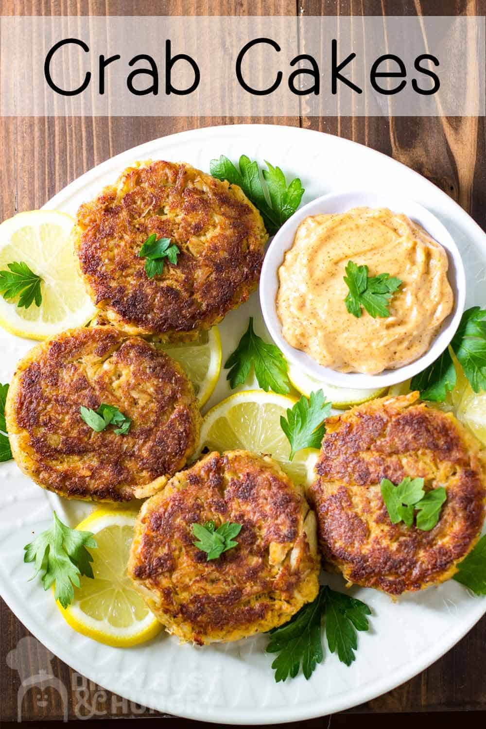 Overhead shot of four crab cakes in a circle on a white plate with a bowl or dipping sauce on the side on a bed of sliced lemons and herbs.