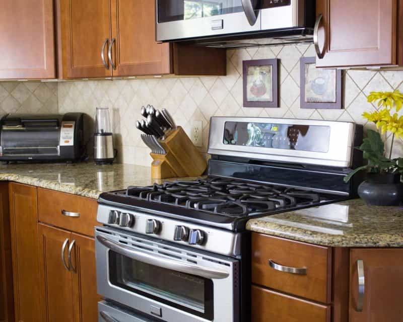 photo of a kitchen stove and granite countertops, with blender, toaster oven, and knife set
