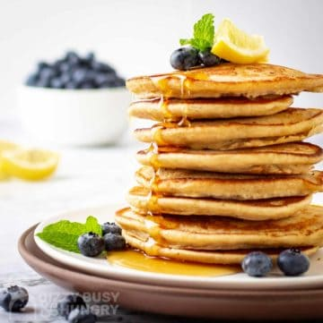Side view of multiple lemon pancakes stacked on a white plate garnished with mint, lime, syrup, and blueberries.